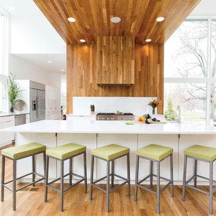 シンシナティの大きいコンテンポラリースタイルのおしゃれなキッチン (フラットパネル扉のキャビネット、白いキャビネット、シルバーの調理設備の、アンダーカウンターシンク、人工大理石カウンター、白いキッチンパネル、ガラス板のキッチンパネル、無垢フローリング、茶色い床、グレーのキッチンカウンター) の写真
