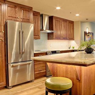 Foto di una cucina classica di medie dimensioni con ante con bugna sagomata, ante in legno bruno, top in quarzite, paraspruzzi bianco, paraspruzzi con piastrelle di vetro, elettrodomestici in acciaio inossidabile, parquet chiaro, isola e lavello a tripla vasca