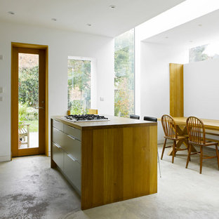 Medium sized contemporary kitchen/diner in London with flat-panel cabinets, concrete flooring, an island, grey floors, brown worktops, white cabinets and wood worktops.