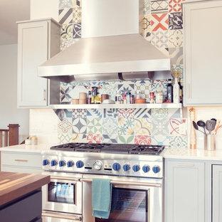 シーダーラピッズの大きいエクレクティックスタイルのおしゃれなキッチン (シングルシンク、シェーカースタイル扉のキャビネット、グレーのキャビネット、大理石カウンター、白いキッチンパネル、サブウェイタイルのキッチンパネル、シルバーの調理設備の、淡色無垢フローリング、茶色い床) の写真