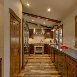 サクラメントの中サイズのシャビーシック調のおしゃれなキッチン (シングルシンク、シェーカースタイル扉のキャビネット、中間色木目調キャビネット、クオーツストーンカウンター、ベージュキッチンパネル、サブウェイタイルのキッチンパネル、シルバーの調理設備、無垢フローリング、アイランドなし) の写真