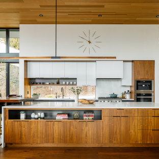 Idéer för retro vitt kök, med släta luckor, vita skåp, vitt stänkskydd, rostfria vitvaror, en köksö och brunt golv