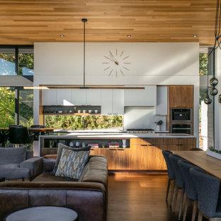 Idéer för att renovera ett 50 tals vit vitt kök, med släta luckor, vita skåp, vitt stänkskydd, rostfria vitvaror, en köksö och brunt golv