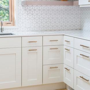 Immagine di una cucina ad U scandinava di medie dimensioni con lavello a doppia vasca, ante lisce, ante bianche, paraspruzzi bianco, paraspruzzi con piastrelle in ceramica, elettrodomestici in acciaio inossidabile, parquet chiaro, nessuna isola, pavimento giallo e top bianco
