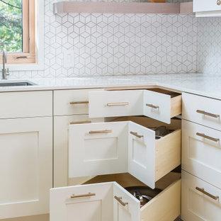 ミネアポリスの中くらいの北欧スタイルのおしゃれなコの字型キッチン (ダブルシンク、フラットパネル扉のキャビネット、白いキャビネット、白いキッチンパネル、セラミックタイルのキッチンパネル、シルバーの調理設備、淡色無垢フローリング、アイランドなし、黄色い床、白いキッチンカウンター) の写真