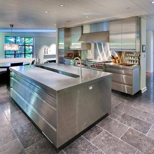Diseño de cocina comedor urbana con electrodomésticos de acero inoxidable, puertas de armario en acero inoxidable, encimera de acero inoxidable, fregadero integrado, armarios con paneles lisos, salpicadero metalizado y salpicadero de metal