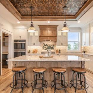 Klassische Küche mit Unterbauwaschbecken, Schrankfronten im Shaker-Stil, weißen Schränken, Quarzwerkstein-Arbeitsplatte, Küchenrückwand in Weiß, Rückwand aus Steinfliesen, Küchengeräten aus Edelstahl, Vinylboden, Kücheninsel, weißer Arbeitsplatte und braunem Boden in Grand Rapids