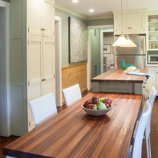 Traditional eat-in kitchen designs - Inspiration for a timeless dark wood floor eat-in kitchen remodel in New York with shaker cabinets, beige cabinets, wood countertops and stainless steel appliances