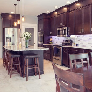 Photo of a traditional single-wall eat-in kitchen in Cedar Rapids with an undermount sink, recessed-panel cabinets, dark wood cabinets, quartz benchtops, metallic splashback, mosaic tile splashback, stainless steel appliances, with island, white floor, white benchtop and porcelain floors.