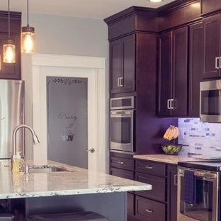 Exemple d'une cuisine américaine linéaire craftsman avec un évier encastré, un placard avec porte à panneau encastré, des portes de placard en bois sombre, un plan de travail en quartz modifié, une crédence métallisée, une crédence en mosaïque, un électroménager en acier inoxydable, un sol en carrelage de porcelaine, un îlot central, un sol blanc et un plan de travail blanc.