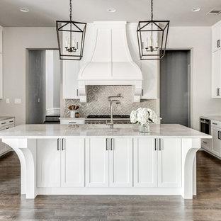 ダラスの大きい地中海スタイルのおしゃれなキッチン (ドロップインシンク、シェーカースタイル扉のキャビネット、白いキャビネット、珪岩カウンター、ベージュキッチンパネル、セラミックタイルのキッチンパネル、シルバーの調理設備の、無垢フローリング、茶色い床、ベージュのキッチンカウンター) の写真