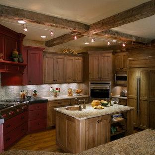 На фото: п-образная кухня-гостиная среднего размера в стиле рустика с одинарной раковиной, фасадами с утопленной филенкой, красными фасадами, разноцветным фартуком, техникой из нержавеющей стали, фартуком из сланца, гранитной столешницей, паркетным полом среднего тона, коричневым полом, двумя и более островами, бежевой столешницей и балками на потолке с