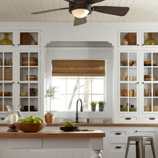 This is an example of a small country galley separate kitchen in New York with an undermount sink, open cabinets, white cabinets, wood benchtops, white splashback, cement tile splashback, stainless steel appliances, medium hardwood floors and with island.