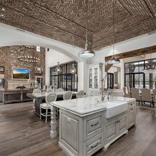 フェニックスの巨大なシャビーシック調のおしゃれなキッチン (エプロンフロントシンク、レイズドパネル扉のキャビネット、淡色木目調キャビネット、大理石カウンター、マルチカラーのキッチンパネル、磁器タイルのキッチンパネル、パネルと同色の調理設備、濃色無垢フローリング、茶色い床、マルチカラーのキッチンカウンター) の写真