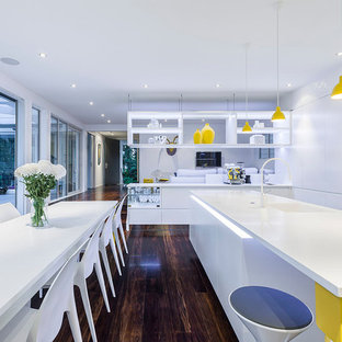 Photo of a contemporary kitchen in Christchurch with an undermount sink, flat-panel cabinets, white cabinets, yellow splashback, white appliances, dark hardwood floors and multiple islands.