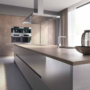 Photo of an expansive modern single-wall open plan kitchen in London with an integrated sink, flat-panel cabinets, beige cabinets, concrete benchtops, beige splashback, panelled appliances, porcelain floors and with island.