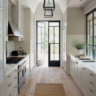 Diseño de cocina de galera, tradicional, sin isla, con fregadero de doble seno, armarios estilo shaker, puertas de armario blancas, encimera de mármol, salpicadero blanco y suelo de madera clara