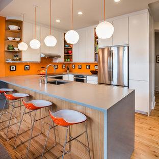 Modelo de cocina en U, actual, con fregadero bajoencimera, armarios con paneles lisos, puertas de armario blancas, salpicadero naranja, electrodomésticos de acero inoxidable, suelo de madera clara y península