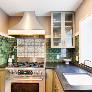 Photo of a small transitional l-shaped separate kitchen in Philadelphia with an undermount sink, glass-front cabinets, green splashback, subway tile splashback, stainless steel appliances, no island, green cabinets, granite benchtops and porcelain floors.