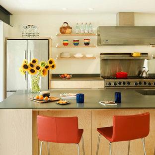Foto de cocina de galera, minimalista, abierta, con fregadero bajoencimera, armarios con paneles lisos, electrodomésticos de acero inoxidable, suelo de madera en tonos medios, una isla, puertas de armario de madera clara, encimera de acrílico y encimeras marrones