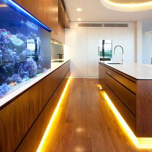 Ejemplo de cocina comedor contemporánea con armarios con paneles lisos, electrodomésticos de acero inoxidable y puertas de armario de madera en tonos medios