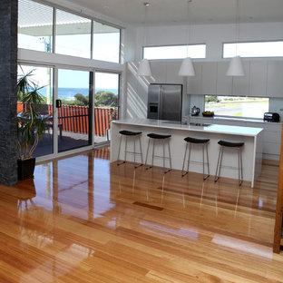 Zweizeilige, Mittelgroße Moderne Wohnküche mit Einbauwaschbecken, Schrankfronten mit vertiefter Füllung, weißen Schränken, Arbeitsplatte aus Recyclingglas, Küchengeräten aus Edelstahl, braunem Holzboden und Kücheninsel in Sydney