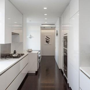 Foto de cocina comedor de galera, actual, de tamaño medio, con armarios con paneles con relieve, puertas de armario blancas, salpicadero beige, electrodomésticos de acero inoxidable y suelo de madera oscura