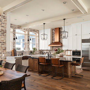 Large transitional eat-in kitchen ideas - Eat-in kitchen - large transitional galley light wood floor and beige floor eat-in kitchen idea in Phoenix with an undermount sink, shaker cabinets, white cabinets, quartz countertops, brown backsplash, brick backsplash, stainless steel appliances, an island and black countertops