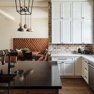 フェニックスの広いトランジショナルスタイルのおしゃれなキッチン (アンダーカウンターシンク、シェーカースタイル扉のキャビネット、白いキャビネット、クオーツストーンカウンター、茶色いキッチンパネル、レンガのキッチンパネル、シルバーの調理設備、淡色無垢フローリング、ベージュの床、黒いキッチンカウンター) の写真