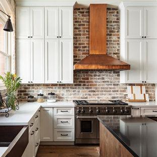 Idéer för ett stort klassiskt vit kök, med en undermonterad diskho, vita skåp, bänkskiva i kvarts, brunt stänkskydd, stänkskydd i tegel, rostfria vitvaror, en köksö, luckor med infälld panel, mellanmörkt trägolv och brunt golv