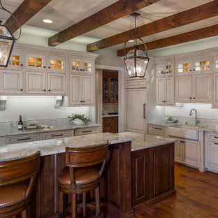 Inspiration for a country l-shaped open plan kitchen in Austin with a farmhouse sink, raised-panel cabinets, white cabinets, granite benchtops, white splashback, ceramic splashback, stainless steel appliances, medium hardwood floors and with island.