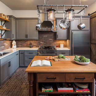 Idee per una grande cucina industriale chiusa con lavello sottopiano, ante grigie, top in superficie solida, elettrodomestici in acciaio inossidabile, pavimento in mattoni, ante in stile shaker, paraspruzzi marrone, paraspruzzi in mattoni e pavimento marrone