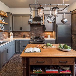 Foto på ett avskilt, stort industriellt l-kök, med en undermonterad diskho, grå skåp, bänkskiva i koppar, rostfria vitvaror, tegelgolv, en köksö, skåp i shakerstil, brunt stänkskydd, stänkskydd i tegel och brunt golv