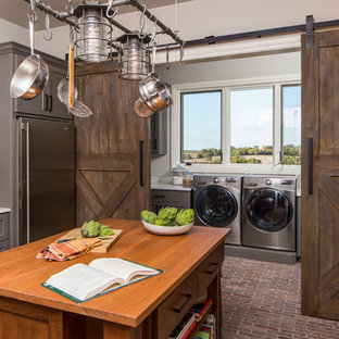 Large industrial enclosed kitchen pictures - Enclosed kitchen - large industrial l-shaped brick floor and brown floor enclosed kitchen idea in Austin with an undermount sink, gray cabinets, stainless steel appliances, an island, shaker cabinets, wood countertops, brown backsplash and brick backsplash