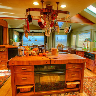 Example of a huge eclectic u-shaped light wood floor eat-in kitchen design in Seattle with a farmhouse sink, recessed-panel cabinets, medium tone wood cabinets, granite countertops, multicolored backsplash, stone slab backsplash, stainless steel appliances and an island