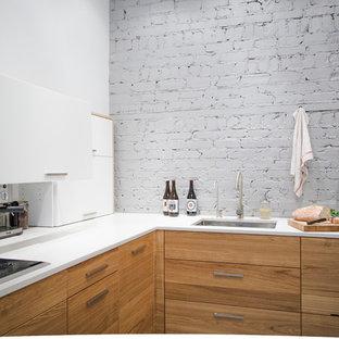 モントリオールのコンテンポラリースタイルのおしゃれなキッチン (アンダーカウンターシンク、フラットパネル扉のキャビネット、中間色木目調キャビネット、ラミネートカウンター、シルバーの調理設備、グレーのキッチンパネル、レンガのキッチンパネル) の写真