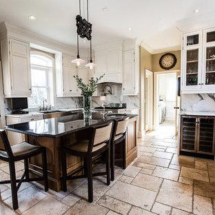 Неиссякаемый источник вдохновения для домашнего уюта: отдельная, п-образная кухня в стиле кантри с раковиной в стиле кантри, фасадами с утопленной филенкой, белыми фасадами, мраморной столешницей, белым фартуком, фартуком из каменной плиты, техникой из нержавеющей стали, полом из известняка и островом