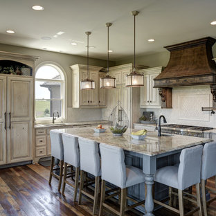 Elegant l-shaped dark wood floor and brown floor kitchen photo in Other with an undermount sink, raised-panel cabinets, beige cabinets, white backsplash, paneled appliances, an island and beige countertops