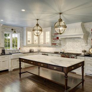 Inspiration för klassiska beige l-kök, med en rustik diskho, luckor med infälld panel, beige skåp, marmorbänkskiva, grått stänkskydd, stänkskydd i marmor, rostfria vitvaror, mörkt trägolv, en köksö och brunt golv