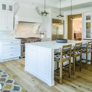 Immagine di una cucina a L classica con ante con bugna sagomata, ante bianche, paraspruzzi bianco, paraspruzzi in lastra di pietra, elettrodomestici in acciaio inossidabile, parquet chiaro, isola, pavimento beige e top bianco