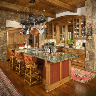 Design ideas for a country l-shaped kitchen in Other with a farmhouse sink, raised-panel cabinets, medium wood cabinets, beige splashback, panelled appliances, medium hardwood floors, with island, brown floor and green benchtop.