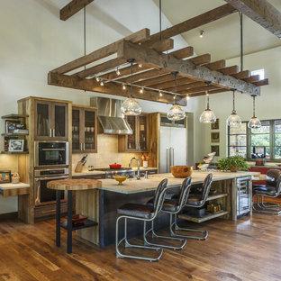 マイアミのラスティックスタイルのおしゃれなキッチン (シェーカースタイル扉のキャビネット、中間色木目調キャビネット、ベージュキッチンパネル、サブウェイタイルのキッチンパネル、シルバーの調理設備の、無垢フローリング、茶色い床、ベージュのキッチンカウンター) の写真