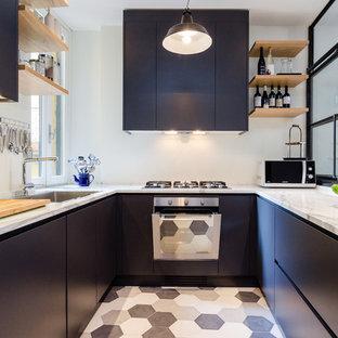 Ispirazione per una cucina ad U industriale di medie dimensioni con lavello a vasca singola, ante lisce, elettrodomestici in acciaio inossidabile, nessuna isola, ante nere, top in marmo e pavimento con piastrelle in ceramica