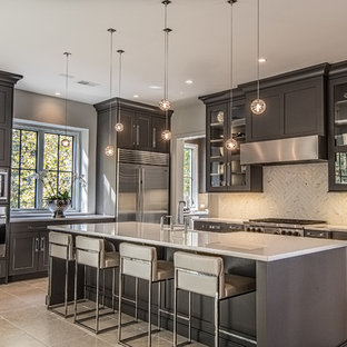 Mid-sized transitional l-shaped kitchen in Other with a farmhouse sink, shaker cabinets, white splashback, stainless steel appliances, with island, stone tile splashback, porcelain floors and black cabinets.