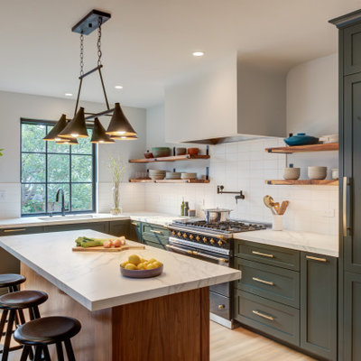 Eat-in kitchen - large transitional l-shaped light wood floor and brown floor eat-in kitchen idea in San Francisco with an undermount sink, shaker cabinets, green cabinets, quartz countertops, white backsplash, ceramic backsplash, black appliances, an island and white countertops