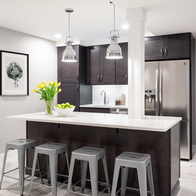 Example of a transitional galley gray floor kitchen design in Philadelphia with an undermount sink, shaker cabinets, dark wood cabinets, white backsplash, stainless steel appliances, an island and white countertops