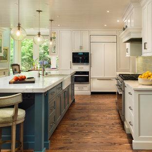 Klassische Küche mit Landhausspüle, Kassettenfronten, weißen Schränken, Marmor-Arbeitsplatte, Küchenrückwand in Grün, Rückwand aus Keramikfliesen, Küchengeräten aus Edelstahl, braunem Holzboden, Kücheninsel und weißer Arbeitsplatte in Philadelphia