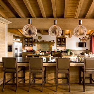 Inspiration pour une grand cuisine américaine chalet en U avec un placard sans porte, des portes de placard en bois brun, une crédence verte, une crédence en carrelage métro, un électroménager en acier inoxydable, un sol en bois brun et un îlot central.