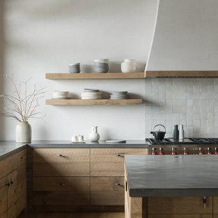 Rustikale Küche in L-Form mit flächenbündigen Schrankfronten, hellbraunen Holzschränken, Küchenrückwand in Grau, Rückwand aus Mosaikfliesen, Küchengeräten aus Edelstahl, hellem Holzboden, Kücheninsel, beigem Boden und grauer Arbeitsplatte in Sonstige