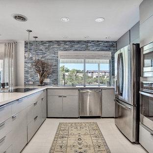 オースティンの中くらいのモダンスタイルのおしゃれなキッチン (アンダーカウンターシンク、グレーのキャビネット、クオーツストーンカウンター、青いキッチンパネル、ボーダータイルのキッチンパネル、シルバーの調理設備、セラミックタイルの床、フラットパネル扉のキャビネット) の写真